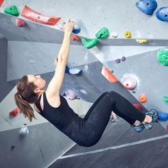 Woman on rock climbing wall at The Climbing Hangar